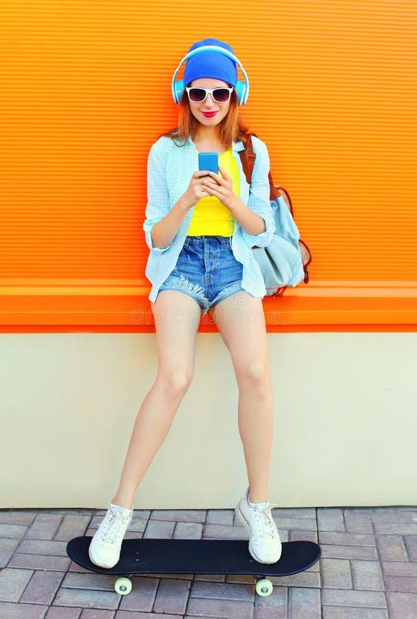 Kühles Mädchen der Mode recht hört Musik unter Verwendung des Smartphone auf Skateboard über bunter Orange stockfotografie