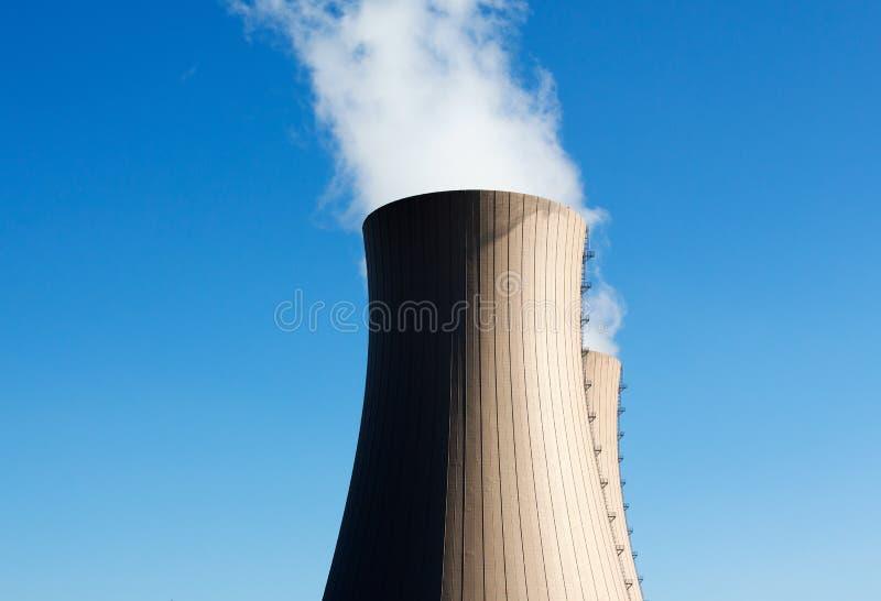 Kühltürme des Atomkraftwerks gegen blauen Himmel stockbild