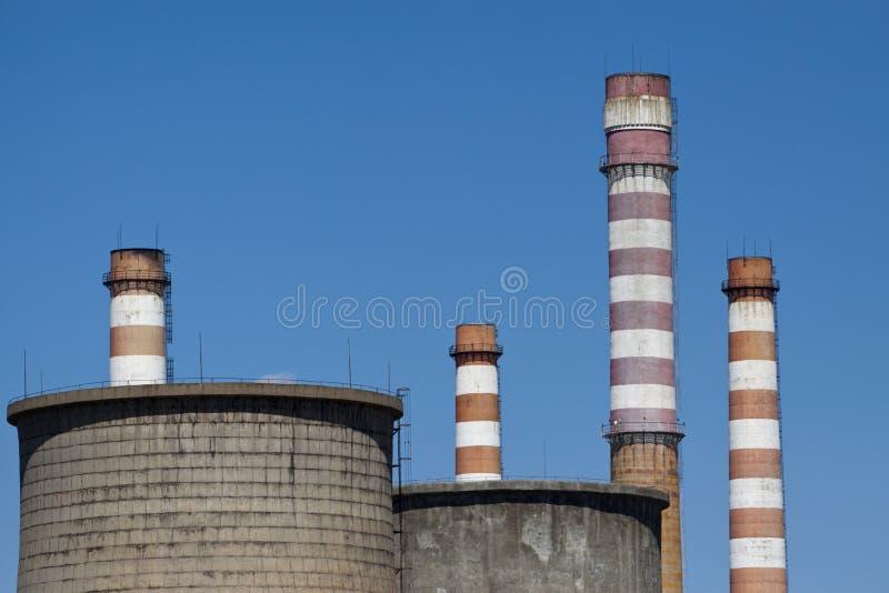 Kühltürme und Fabrikschornsteine gegen blauen Himmel stockfotos