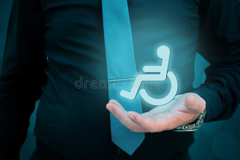 Kümmern von  um Personen mit Unfähigkeitskonzept Geschäftsmann, der hologramic weelchair in seiner Hand hält lizenzfreies stockbild