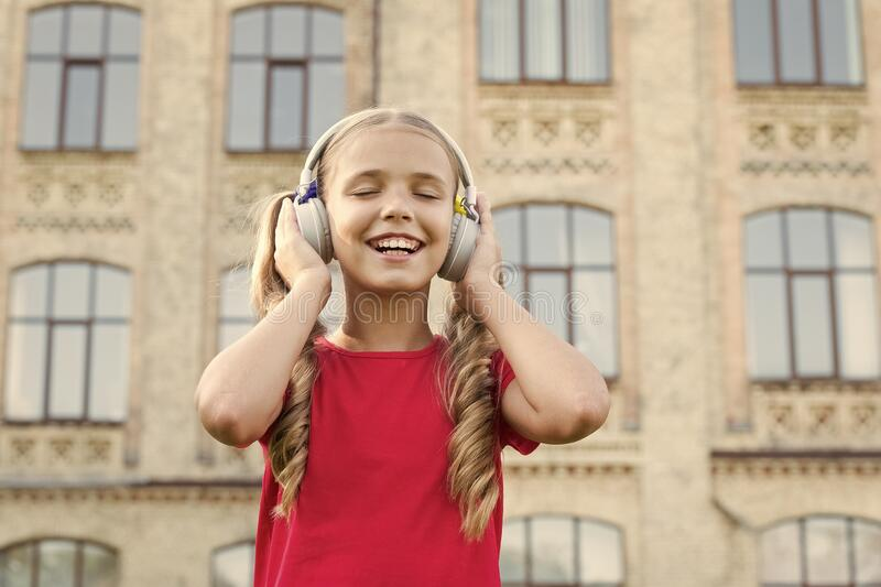 Künftiger berühmter Sänger Von Musik inspiriert Girl-Hörmusik - modernes Gadget Kleines Kind mit kabellosem Kopfhörer Stereo stockbild
