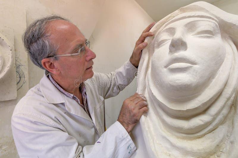 Künstler bei der Arbeit im Studio auf einer Skulptur des Gesichtes lizenzfreie abbildung