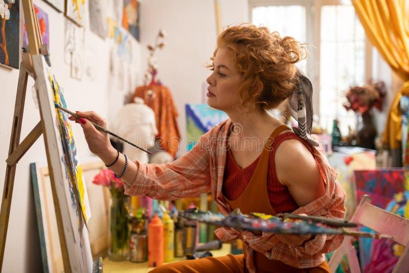 Künstler, der das stilvolle Hemdgefühl mit einbezogen in Malerei trägt lizenzfreie stockfotos