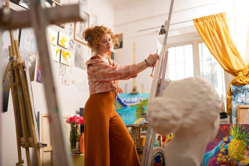 Künstler, der die Inspiration malt auf dem Segeltuch steht nahe Fenster hat lizenzfreie stockbilder