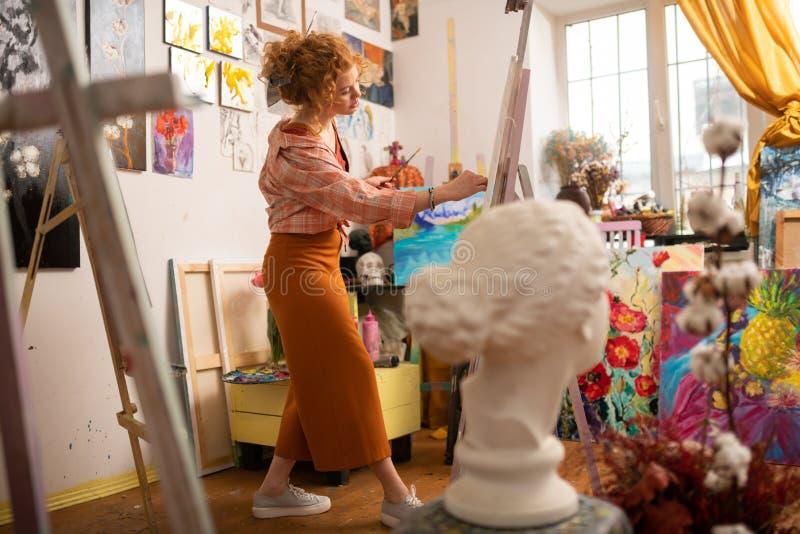 Künstler, der die stilvolle Ausstattung arbeitet in der künstlerischen Werkstatt trägt lizenzfreie stockfotografie
