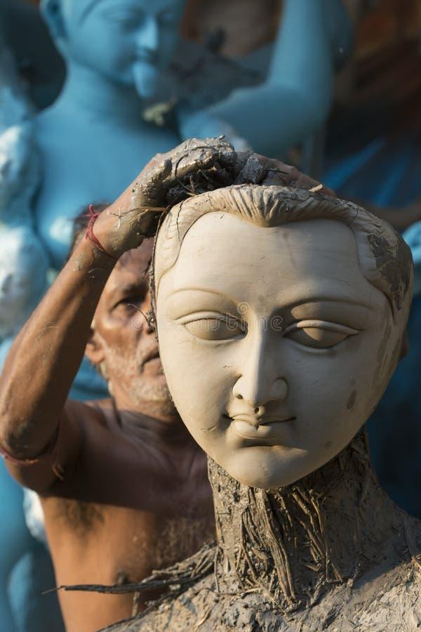 Künstler, der an einem Hauptteil Idolen eines Lehms der hindischen Göttin bei Kumartuli, Kolkata, Indien arbeitet lizenzfreies stockbild