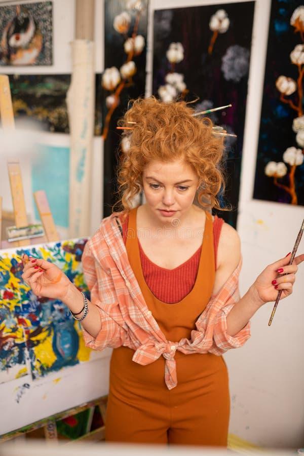 Künstler, der etwas Zögern beim Wählen von Farbe hat stockfotos