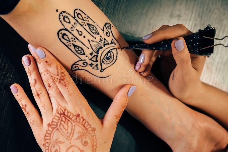 Künstler, der Hennastrauch mehndi Tätowierung auf weiblicher Hand anwendet lizenzfreie stockbilder