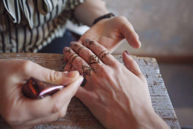 Künstler, der Hennastrauchtätowierung auf Frauenhänden anwendet stockbild