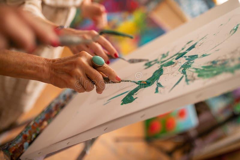 Künstler, der Malereipalette mit Gouache bei der Färbung des Bildes hält stockbild