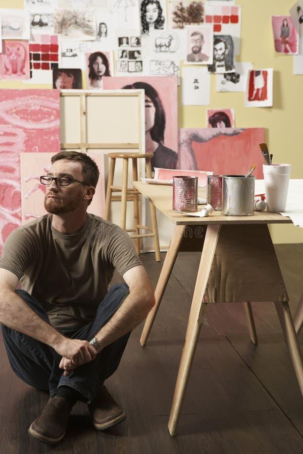 Künstler, der nahe bei Tabelle sitzt stockfoto