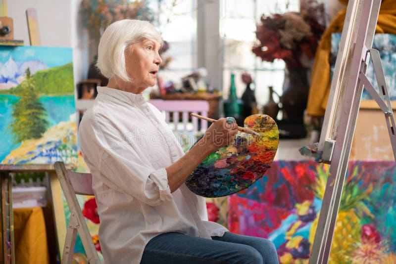 Künstler, der nahe Segeltuch sitzt und an neues Meisterwerk denkt stockbilder