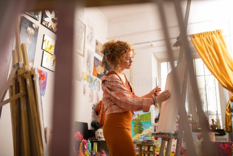 Künstler, der quadratische Hemdmalerei auf Segeltuch in der Werkstatt trägt lizenzfreie stockfotos