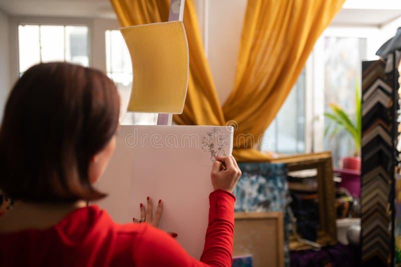 Künstler, der roten Kleiderholdingbleistift und -c$zeichnen trägt lizenzfreies stockbild