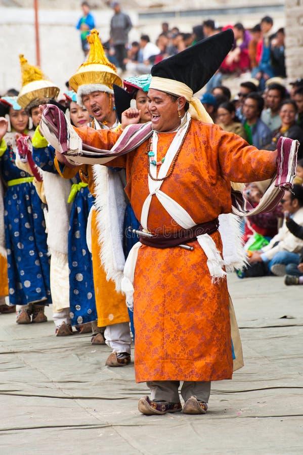 Künstler in der tibetanischen Kleidung, die Volkstanz durchführt stockfotografie