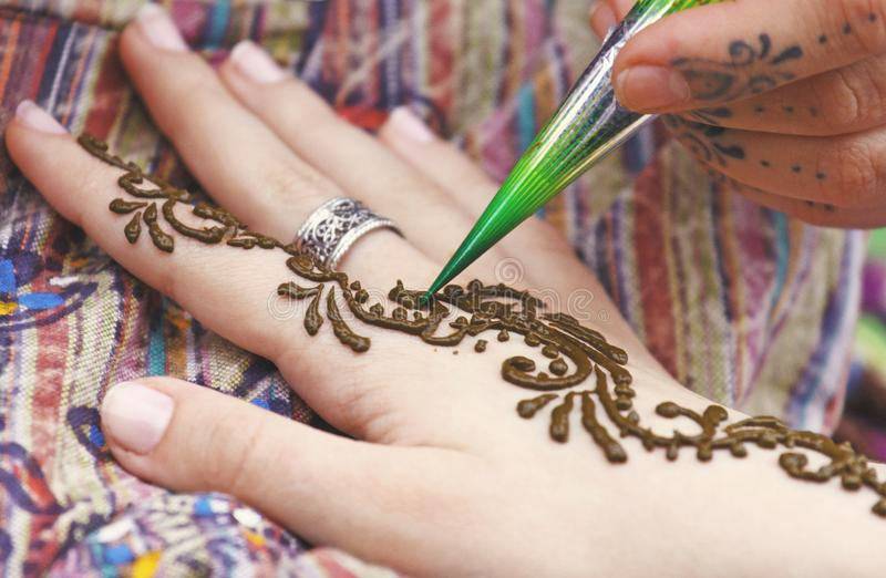 Künstler, der traditionelle indische Hennastrauchtätowierung auf Frauenhand malt lizenzfreie stockbilder