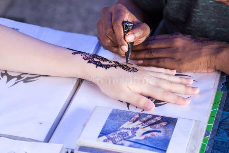 Künstler, der vorübergehende Hennastrauch mehendi Tätowierungskunst auf Handflosse verpflanzt stockfotografie