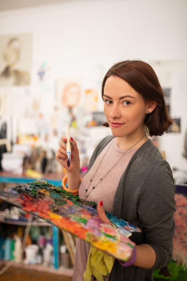Künstler mit dem Pendelschnitt, der Farbpalette und -bürste hält stockbild