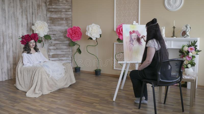 Künstler zeichnet ein Porträt von der Natur Schönes Modell, wenn ein Kranz des Scharlachrots Pfingstrose auf seinem Kopf, das Sit lizenzfreie stockfotografie