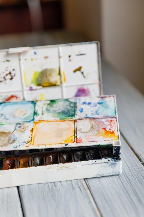 Künstlerarbeitsplatz: Weiße Tabelle eines Künstlers mit Kunstwerkzeugen für das Zeichnen stockbild