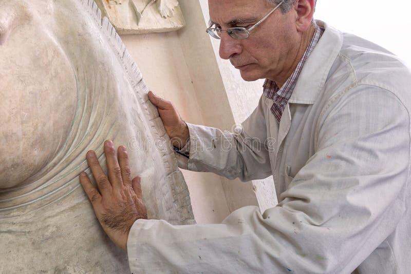 Künstlergeste mit den Händen auf einer Skulptur im Kunststudio lizenzfreie stockfotografie