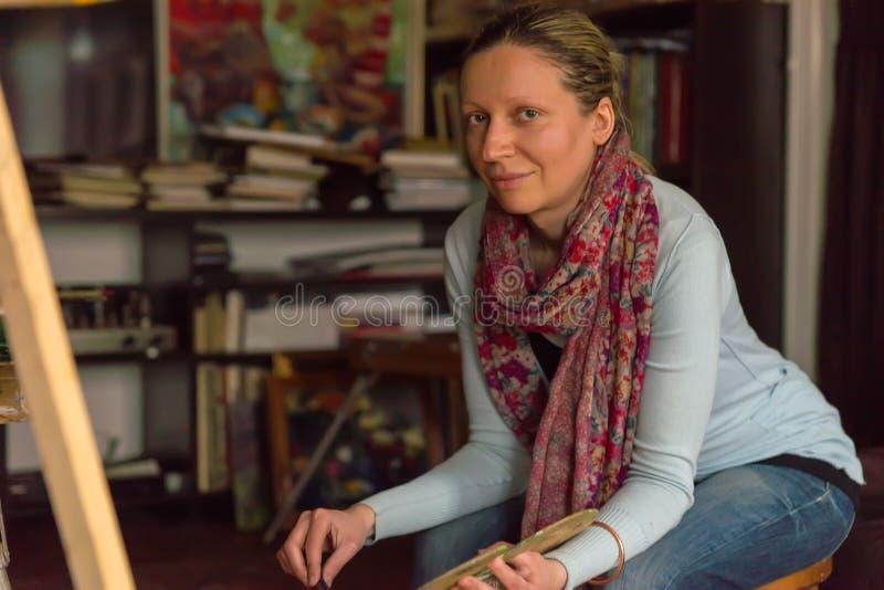 Künstlerin, die die Kamera in einem Studio betrachtend sitzt lizenzfreies stockfoto