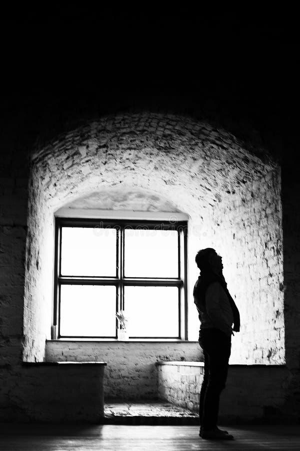 Künstlerisches körniges Bewegungsunschärfebild des Schattenbildes der Personenstellung vor altem Fenster lizenzfreie stockfotos