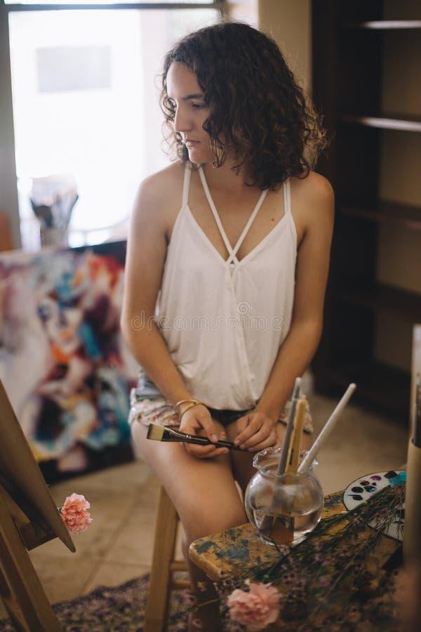 Künstlermädchen malt Bild auf Segeltuch im Studio stockbild