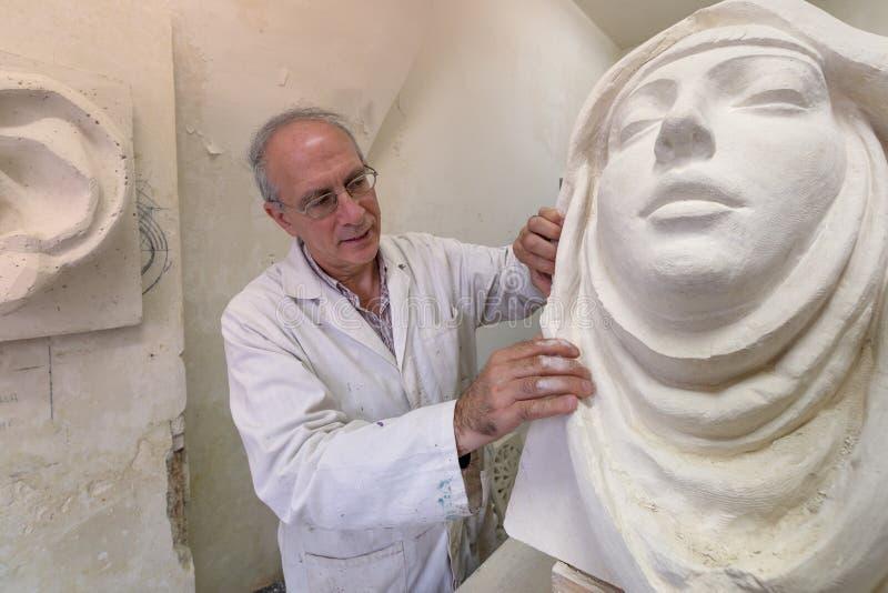 Künstlermeister bei der Arbeit im Studio auf einer Skulptur des Gesichtes stock abbildung