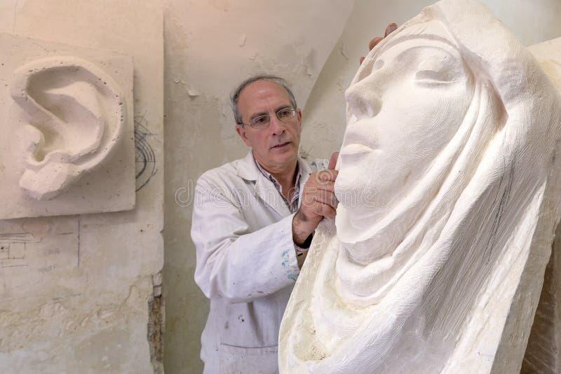 Künstlermeister bei der Arbeit im Studio auf einer Skulptur des Gesichtes stockfoto
