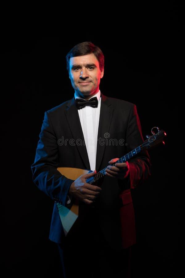 Künstlermusiker, ein dunkelhaariger Mann in einem schwarzen Anzug und eine Fliege, Spiele eine Balalaika stockbild