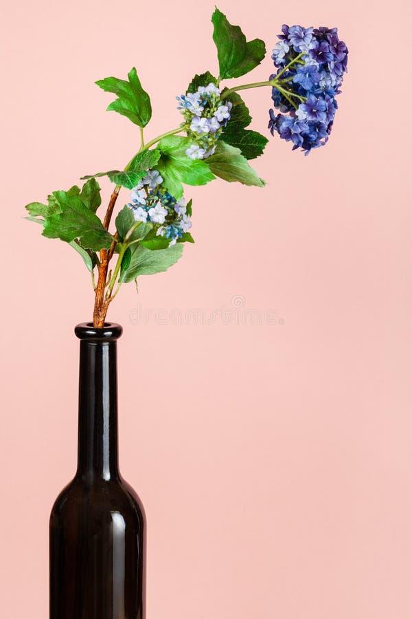 Künstliche Blume in brauner Glasflasche auf Pfirsich stockbilder