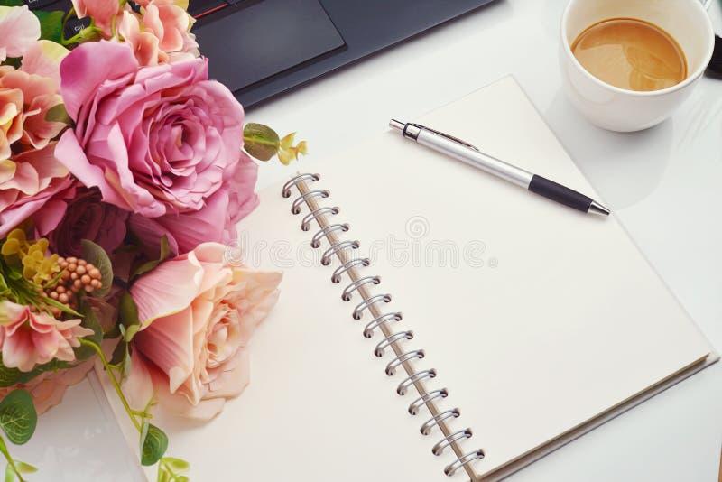 Künstliche Blume der bunten Dekoration, Stift und leeres Notizbuch auf weißem Hintergrund, Draufsicht, Kopienraum für Text lizenzfreie stockfotos