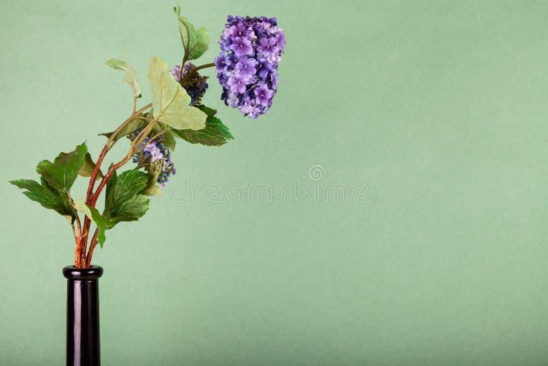 Künstliche Blume in Flasche auf Olivenuntergrund stockfotografie