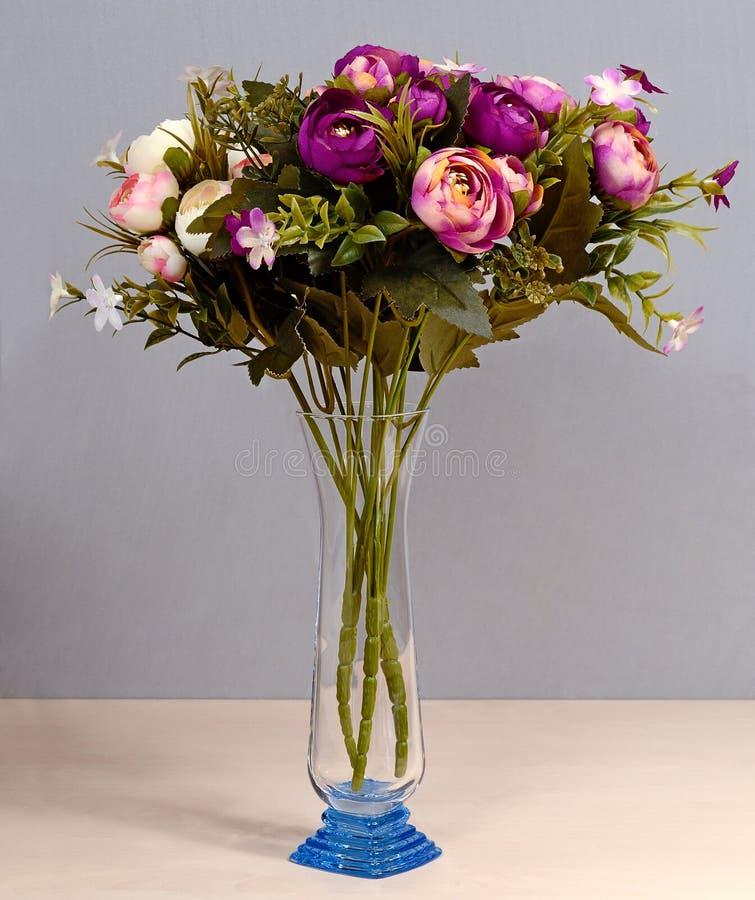 Künstliche Blumen des Glasvase stockfotos