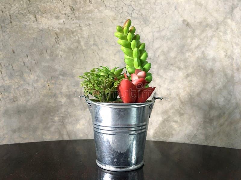 Künstliche Blumen im Aluminiumeimer auf braunem Holztisch lizenzfreies stockfoto