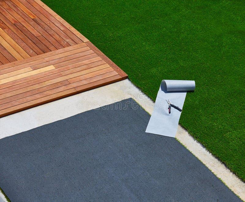 Künstliche Grasinstallation im Plattformgarten mit Werkzeugen lizenzfreies stockfoto
