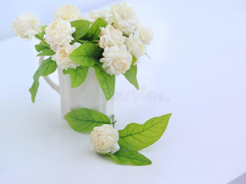 Künstliche Jasminblume im Topf am weißen Tisch mit lizenzfreie stockfotos