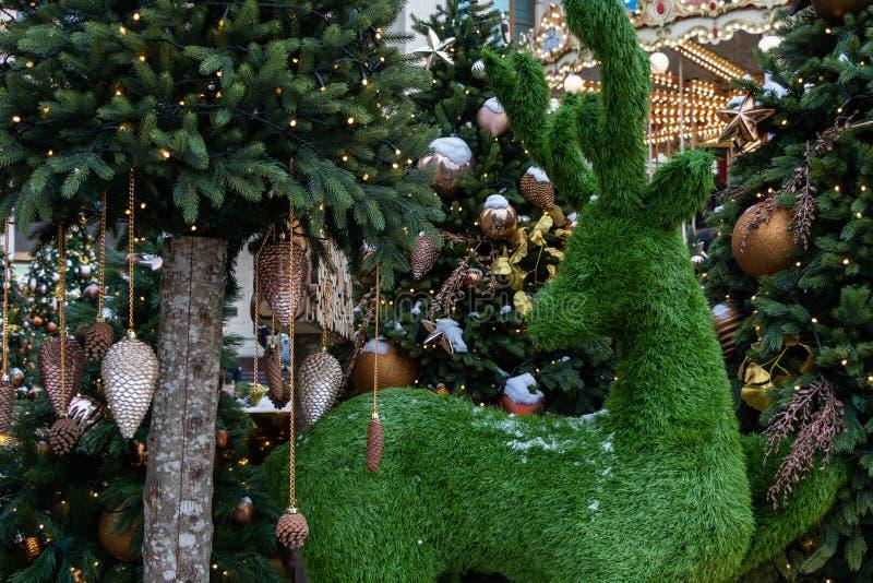 K?nstliche Rotwild nahe dem Weihnachtsbaum Weihnachtsspielwaren auf dem gr?nen Baum mit Schnee Tannenzapfen- und Weihnachtsbaum lizenzfreie stockbilder
