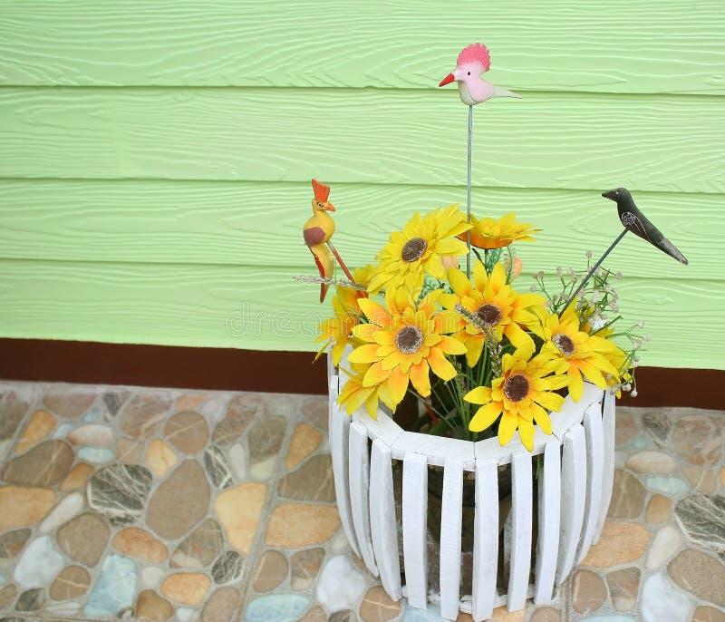 Künstliche Sonnenblume und Baumvogel im weißen hölzernen Topf stockbilder
