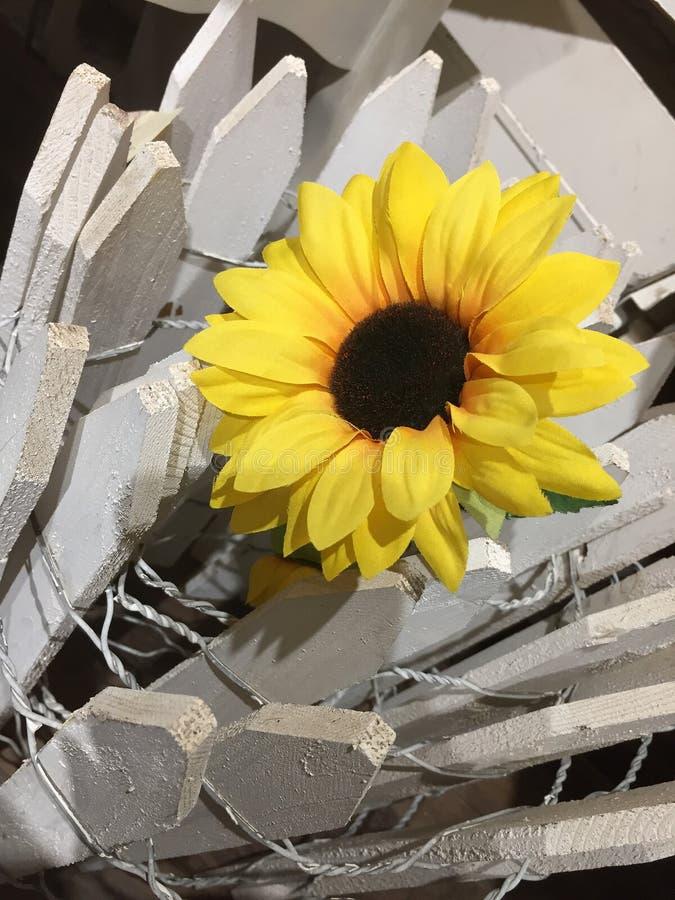 Künstliche Sonnenblume und weißer Zaun lizenzfreies stockfoto