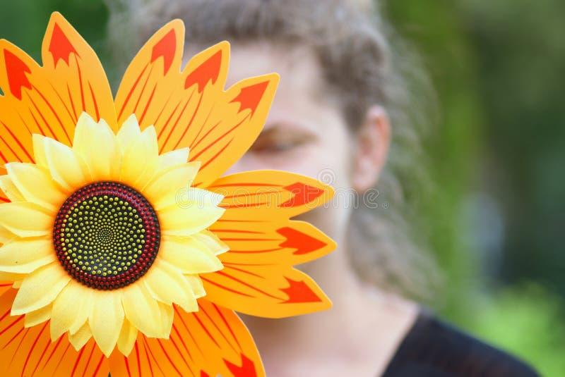 Künstliche Sonnenblume und weibliches Gesicht stockbilder
