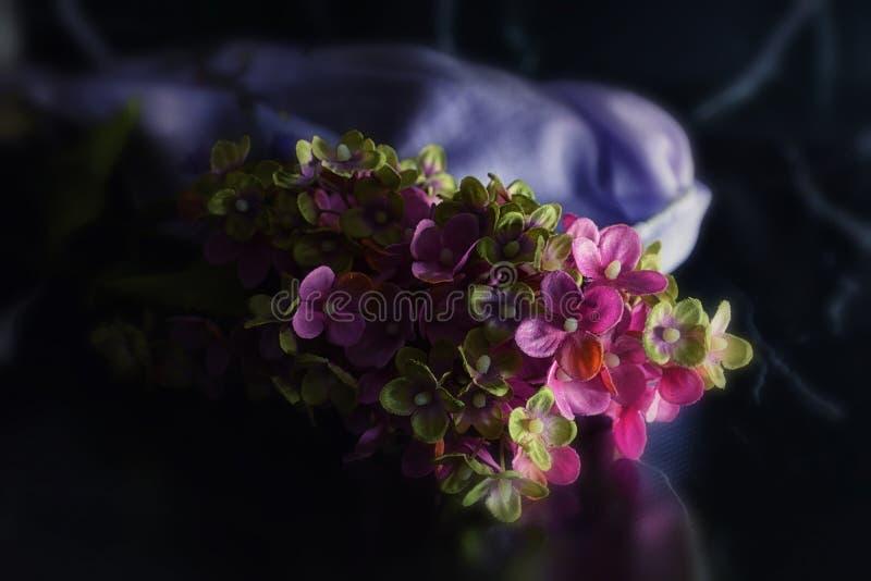 Künstliche violette und grüne Lila-Blumen auf schwarzem Marmorboden stockbilder