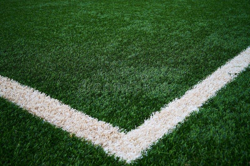 Künstlicher Fußballplatz des grünen Grases mit einer weißen Linie, die wie ein V aber die rechte Seite aussieht, ist etwas ober stockfoto