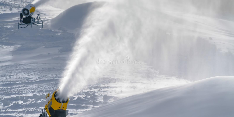 Künstlicher Schnee, der aus Schneekanonen heraus sprüht stockfotos