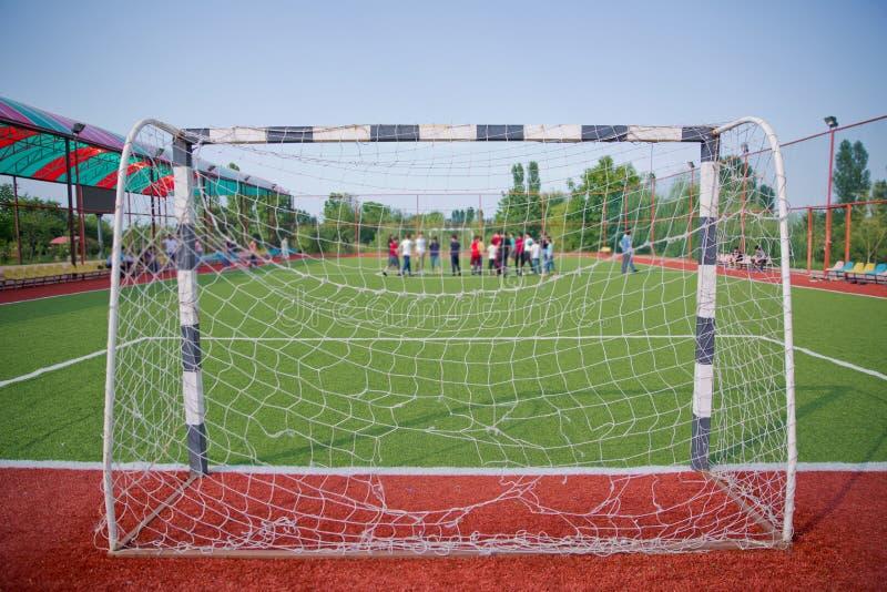Künstliches Gras Mini Football Goal On Ans Defocused Spielerstrafe des Fußballs auf dem Feld klein, Futsals-Spielfeld in der Turn stockbild