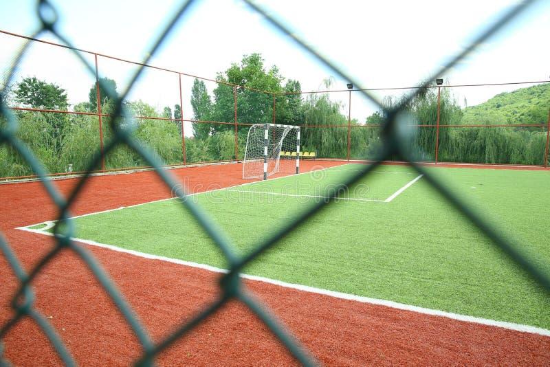 Künstliches Gras Mini Football Goal On Ans Fußballziel auf einem grünen Rasen Fußballplatz nahe Zaun am Tagessonnigen Tag lizenzfreies stockfoto
