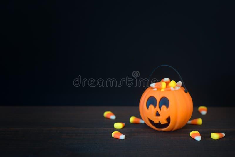Kürbis Halloweens Süßes sonst gibt's Saures gefüllt mit Süßigkeitsmais auf dunkler hölzerner Tabelle und mit schwarzem Hintergrun stockfoto