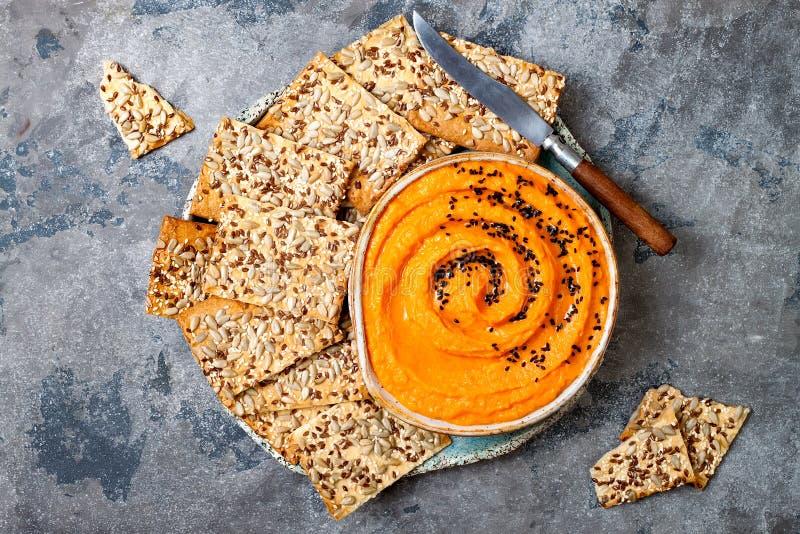 Kürbis hummus würzte mit Olivenöl und schwarzen Samen des indischen Sesams mit ganzen Korncrackern Gesunder vegetarischer Aperiti stockbild