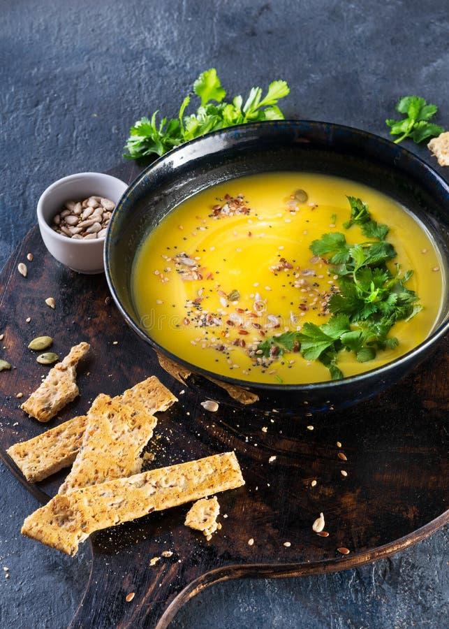 Kürbis und Gemüsesahnesuppe mit Kürbiskernen, Scheiben brot und Petersilie über einem dunklen Hintergrund mit Raum für Text lizenzfreie stockbilder